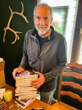 Author Tom Kizza with a stack of books
